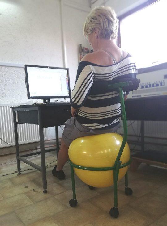 scaun ergonomic cu minge galbena si folosit de o persoana